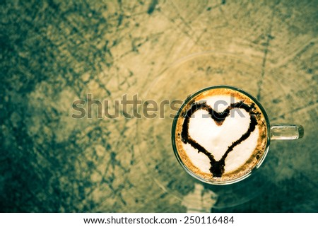 Hot cappuccino coffee with chocolate heart shape on foam, vintage tone  - stock photo