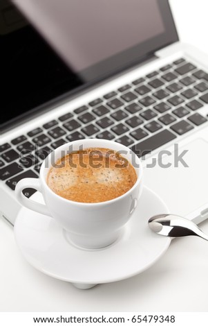 Hot cappuccino cup on laptop - stock photo