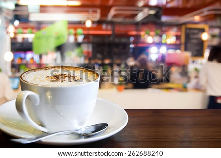 Hot cappuccino on the table with blur coffee shop background - stock photo
