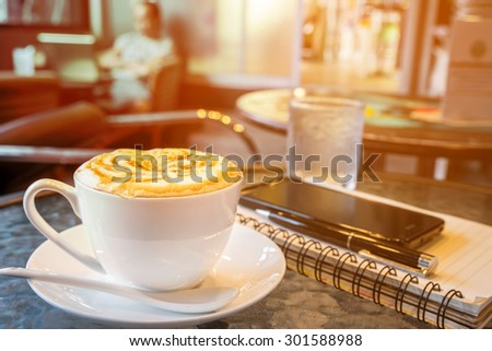 hot Cappuccino on the table with blur coffee shop background, warm vintage tone  - stock photo