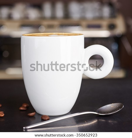 hot Cappuccino on the table with blur coffee shop background, warm vintage tone