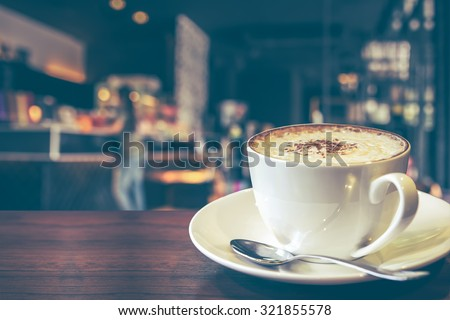 Hot cappuccino on the table with coffee shop background, vintage tone  - stock photo
