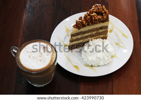 hot capuchino with almond coffee cake on wooden table - stock photo