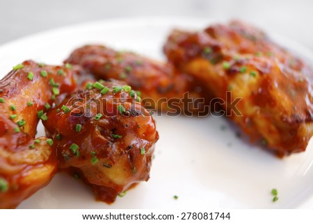 Hot chicken wings on a white ceramic dish. - stock photo