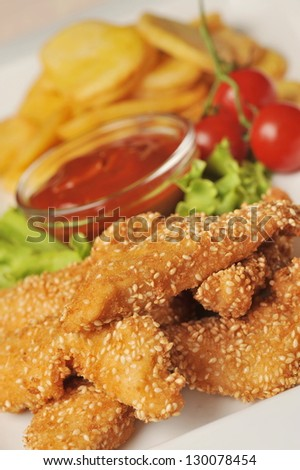 Hot chicken wings with fried potatoes - stock photo
