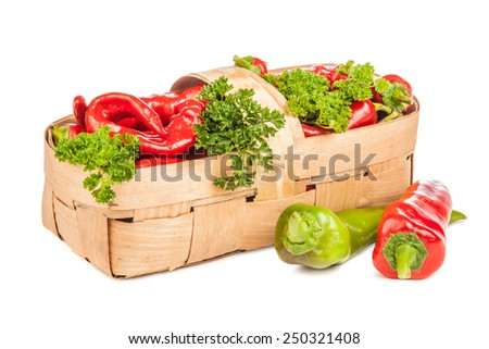 Hot chili pepper, parsley leaves in a wicker wooden basket. Isolated on white background. - stock photo