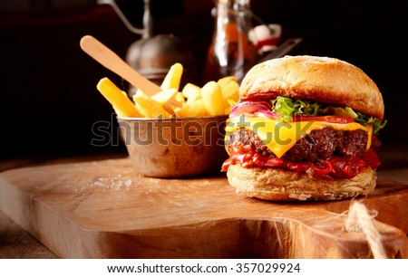 Hot chilli pepper cheeseburger with spicy chili sauce, a beef patty and melted cheese served with a side dish of crispy French Fries on a wooden board in rustic restaurant