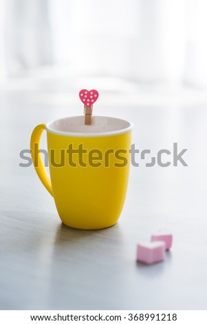 Hot chocolate drink in yellow cup and heart shape marshmellows on wooden floor. - stock photo