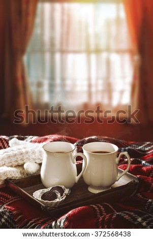 Hot chocolate drinks on tartan rug with winter sunshine filtering through the window - stock photo