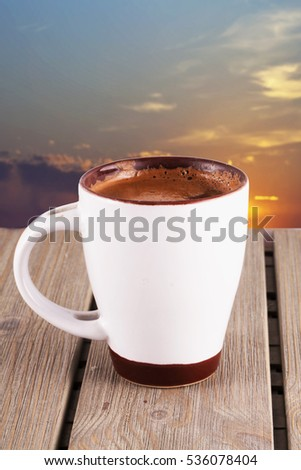 Hot chocolate in a white cup, sunset sky on the background, vertical image