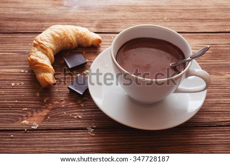 Hot chocolate in a white cup with a croissant on a wooden table