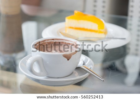 Hot chocolate in cup serve with orange cake ready to eat.