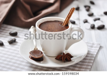 Hot Chocolate in cup with cocoa powder and cinnamon stick on wooden background - stock photo