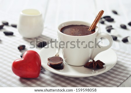 Hot Chocolate in cup with cocoa powder and red stone heart on wooden background