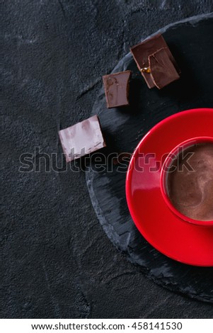 Hot chocolate in red ceramic cup with saucer, served with dark chopped chocolate on round slate stone board over black textured background. With copy space. Top view - stock photo
