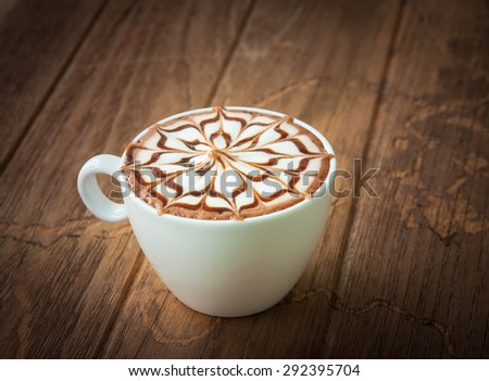 Hot chocolate in white cup with top decorate on wooden background - stock photo