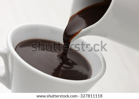 Hot chocolate poured into a white cup on white background - stock photo