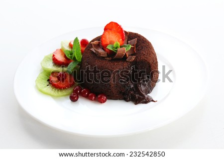 Hot chocolate pudding with fondant centre with fruits, isolated on white - stock photo