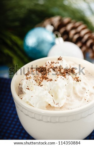 Hot Chocolate topped with whipped cream and cocoa shavings is set against a blue and green background - stock photo