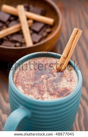 Hot chocolate with a cinnamon stick in a mug - stock photo