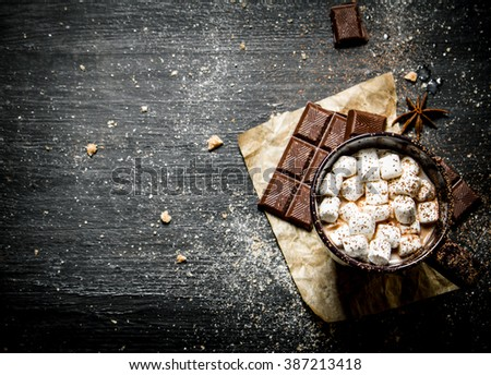 Hot chocolate with bitter chocolate and cinnamon. On a black chalkboard. - stock photo