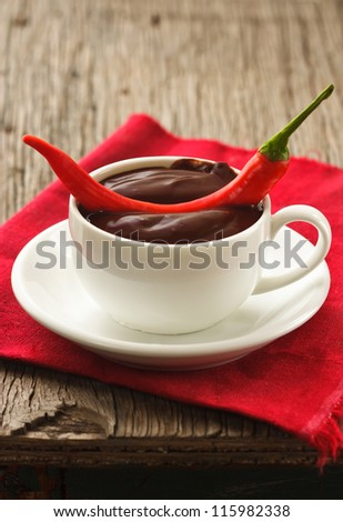 Hot chocolate with chili on an old wooden table. - stock photo