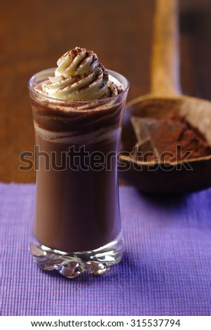 Hot chocolate with cream on purple setting - stock photo