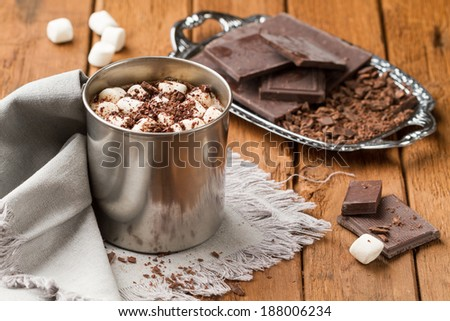Hot chocolate with marshmallows in a tin mug on a wooden table - stock photo