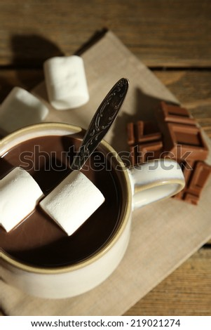 Hot chocolate with marshmallows in mug, on wooden background