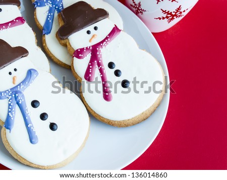 Hot chocolate with peppermint canes and snowman sugar cookies. - stock photo