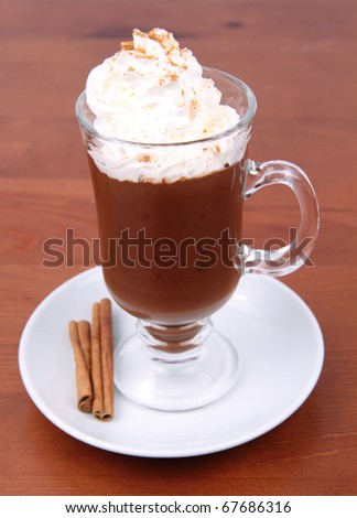 Hot chocolate with whipped cream and cinnamon in a mug on a wooden background - stock photo
