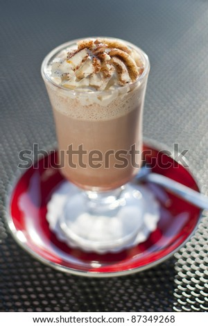 hot chocolate with whipped cream in a glass bowl on high red saucer with a spoon against a dark background - stock photo