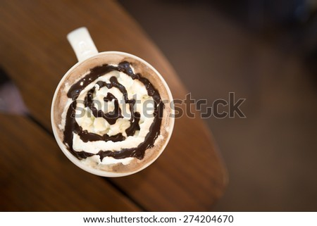 Hot chocolate with whipped cream on wooden table, top view - stock photo