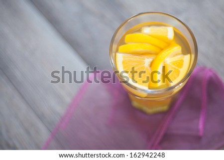 Hot citrus flavor tea served with orange and lemon slices. Full of spices winter time drink on violet tablecloth. - stock photo