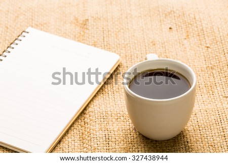 Hot coffee and blank open notebook. - stock photo