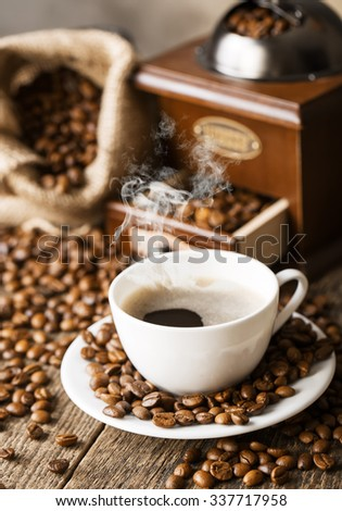 hot coffee and coffee beans on the background of coffee grinders, view from the top