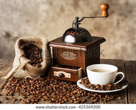 hot coffee and coffee beans on the background of coffee grinders, view from the top - stock photo