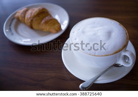 hot coffee and fresh croissant on wooden table
