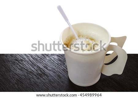Hot coffee cappuccino in disposable paper coffee cup with plastic stirrer on dark wood background - stock photo