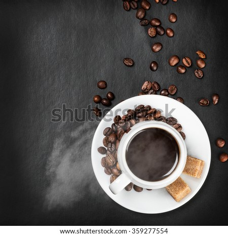 Hot coffee cup on a black background with coffee beans - stock photo