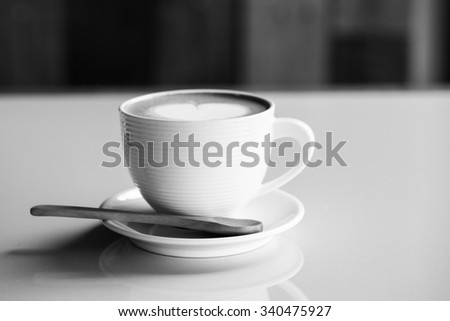 Hot coffee cup with heart shape on surface in black-white tone