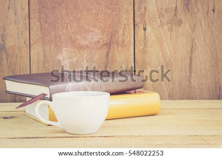 Hot coffee have smoke and book relax time on wood table with copy space. Vintage retro style.