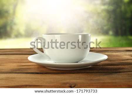 hot coffee in green garden on table