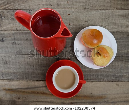 Hot coffee in red cup with muffins on wooden table.