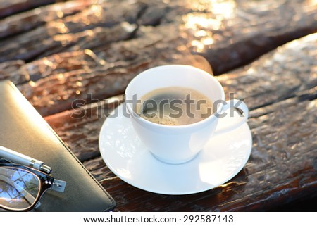 Hot coffee in the cup on old wood table - soft focused