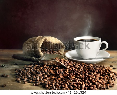 Hot coffee in white coffee cup and coffee beans on wooden table - stock photo
