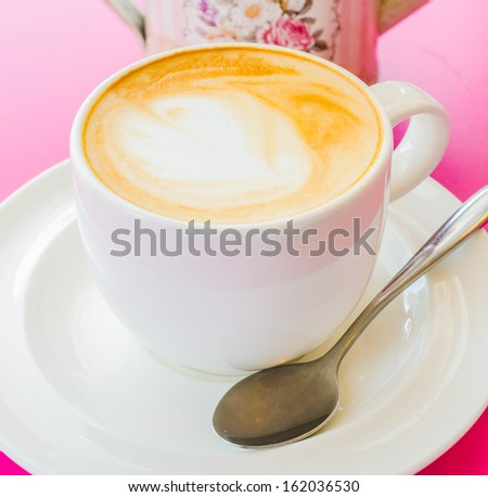 Hot coffee in white cup with fake flower