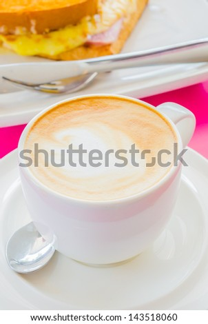 Hot coffee in white cup with sanwich ham&cheese