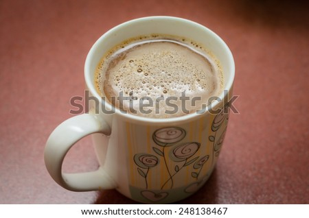 Hot coffee latte in a white mug on reddish brown tile. Shot from top angle of the mug.
