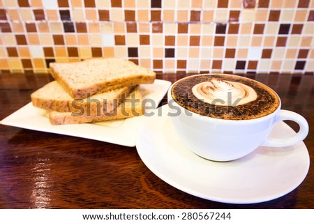 hot coffee mocha latte in white mug  and bread on wood background at  coffee cafe - stock photo